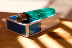 Zigarettenkasten und -feuerzeug auf einer Tabelle Stockfotografie
