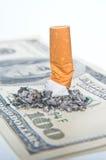 Zigarettenkippe, die auf Geld llaying ist Stockbilder