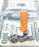 Zigarettenkippe, die auf Geld llaying ist Stockfotografie