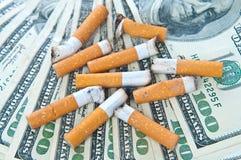 Zigarettenkippen, die auf Geld llaying sind Stockfotografie
