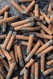 Zigarettenkippen entleert auf Bürgersteig stockbilder