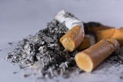 Zigarettenkippen und Asche Stockfotografie