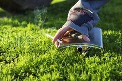Zigarettenraucher, der eine Flasche aufhebt Lizenzfreie Stockfotografie