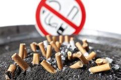 Zigarettenstummel in der Asche mit Nichtraucherzeichen. Stockfotos