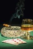 Zigarre angeschaltet Karten und das Getränk im Glas Stockfotografie