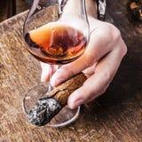 Zigarre in der Mannhand mit Glas Alkohol Stockfoto