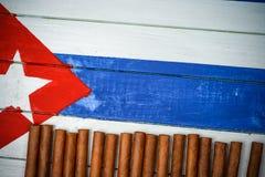 Zigarren auf gemalter kubanischer Staatsflagge Stockbilder