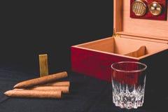 Zigarrenschachtel auf schwarzem Hintergrund und Feuerzeug stockfoto
