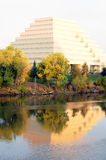 Ziggurat reflected. Orange ziggurat surrounded by trees reflected in blue river stock photography
