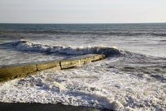 Ziguezague de uma onda do mar que quebram em terra e de um quebra-mar com mar f Foto de Stock Royalty Free
