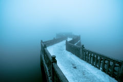 Zigzag bridge in fog. Zigzag bridge on the lake in winter fog stock photography