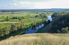 Zigzag river flows between summer valleys Stock Image