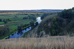 Zigzag river flows between summer valleys Royalty Free Stock Photos