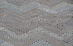 Zigzagpatroon op grijze bakstenenbestrating stock afbeeldingen
