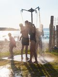 Family on the beach with an open shower royalty free stock image