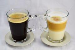 Zij aan zij geneigd koffie zwart-wit - gedraaid door handvatten aan elkaar Stock Foto