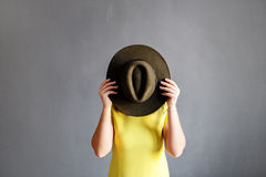 Zij behandelt haar gezicht met een hoed Stock Fotografie