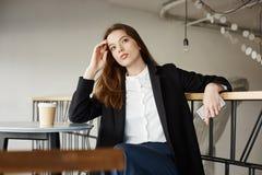 Zij denkt diep over haar toekomst Portret die van modieuze onderneemsterzitting in koffie, op leuning leunen en royalty-vrije stock foto's