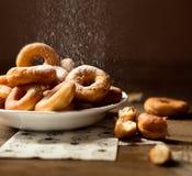 Zij dichte omhooggaand op een bos van verse eigengemaakte donuts met suiker en donkere houten vloer als achtergrond Royalty-vrije Stock Foto
