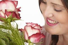 Zij geniet van een boeket van rozen Stock Afbeelding