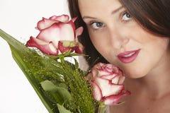 Zij geniet van een boeket van rozen Stock Fotografie