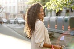 Zij helft-lengte portret van het jonge mooie Afrikaanse meisje die met krullend haar en charmante glimlach opzij in gloed kijken royalty-vrije stock afbeeldingen