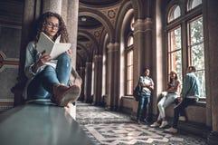 Zij houdt van lezend Mooie vrouwelijke studentenzitting op het traliewerk op de universiteit en het voorbereidingen treffen voor  stock fotografie