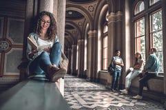 Zij houdt van lezend Mooie vrouwelijke studentenzitting op het traliewerk op de universiteit en het voorbereidingen treffen voor  stock afbeeldingen