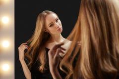 Zij kijkt aan de spiegel van make-upartrist met lichten De glamourluxe kijkt met maniersamenstelling en blond glanzend haar royalty-vrije stock afbeelding