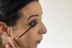 Zij maakt omhoog met de mascara van de oogborstel stock foto's