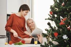 Zij-meningsportret van aantrekkelijke magere overhemd-haired meisje scherpe groenten en het tonen van iets in tablet aan het stock afbeelding