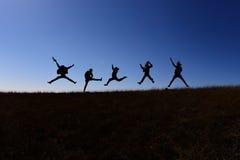 Zij springen terwijl het lopen op een heuvel Royalty-vrije Stock Afbeelding