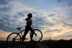 Zijaanzicht atletisch meisje in helm met fiets op rots onder mooie avondhemel met wolken stock afbeeldingen