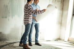 Zijaanzicht bebouwde foto van twee vrolijke kerels die blauwdruk gebruiken op het werk stock afbeeldingen