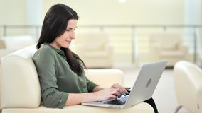Zijaanzicht die mooie toevallige onderneemster glimlachen die gebruikend laptop PC bij woonkamer typen stock footage