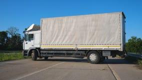 Zijaanzicht die over witte vrachtwagen met ladingsaanhangwagen in midden van weg draaien Vrachtwagenbestuurder die goederen op zi stock footage