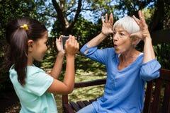 Zijaanzicht die van meisje foto van grootmoeder nemen die gezichten op bank maken Royalty-vrije Stock Foto's
