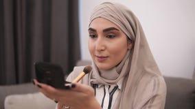 Zijaanzicht die van moslimvrouw die make-up op haar gezicht met borstel doen, oogschaduw toepassen Het moderne leven van moslimme stock videobeelden