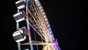Zijaanzicht die van reusachtig Reuzenrad bij pretpark onder donkere nachthemel roteren stock video