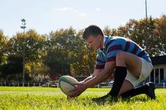 Zijaanzicht die van rugbyspeler klaar om voor doel te schoppen worden royalty-vrije stock afbeelding