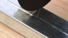 Zijaanzicht die van die schijf om metaal te snijden van de machtshulpmiddel van de hoekmolen een metaalprofiel snijden op de hout stock videobeelden