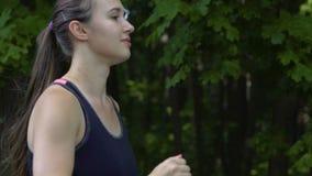 Zijaanzicht die van vrouw in bos, openlucht vrouwelijke agent in verse luchtjogging lopen stock footage