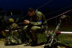 Zijaanzicht ernstig militair het schrijven bericht in telefoon terwijl het dragen in eenvormig en omringd door wapens technologie royalty-vrije stock afbeelding
