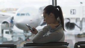 Zijaanzicht jonge mooie vrouw die smartphone in wachtkamer op luchthavenachtergrond gebruiken van vliegtuig in venster stock videobeelden