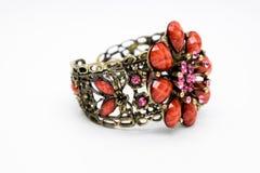 Zijaanzicht mooie armband met gouden roze en rode die stenen op witte achtergrond worden geïsoleerd Stock Foto