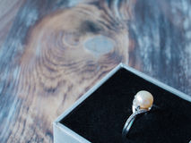 Zijaanzicht over mooie parelring in zwarte doos op houten achtergrond stock foto