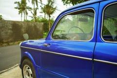 Zijaanzicht over retro blauwe auto in tropische stad De palmen zijn op achtergrond Royalty-vrije Stock Afbeeldingen