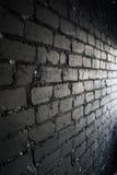 Zijaanzicht over zwarte die bakstenen muur door licht van het venster wordt aangestoken Stock Afbeeldingen