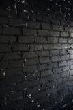 Zijaanzicht over zwarte die bakstenen muur door licht van het venster wordt aangestoken Stock Afbeelding