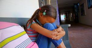 Zijaanzicht van Afrikaans Amerikaans schoolmeisje met hoofd onderaan zitting alleen op bank in schoolgang 4k stock video